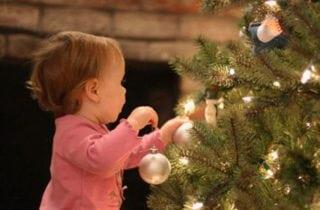 nina jugando en arbol de navidad
